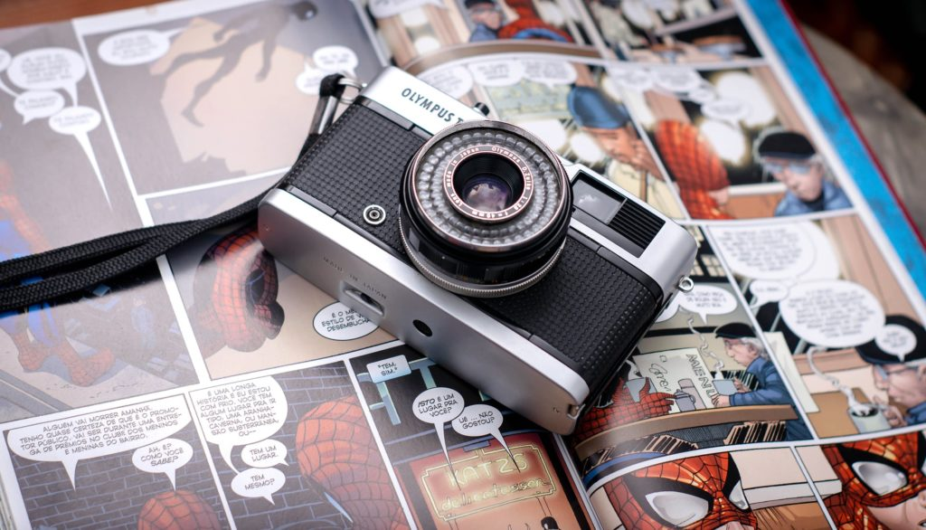 Photo of Olympus camera on top of an opened comic book of Spider-Man